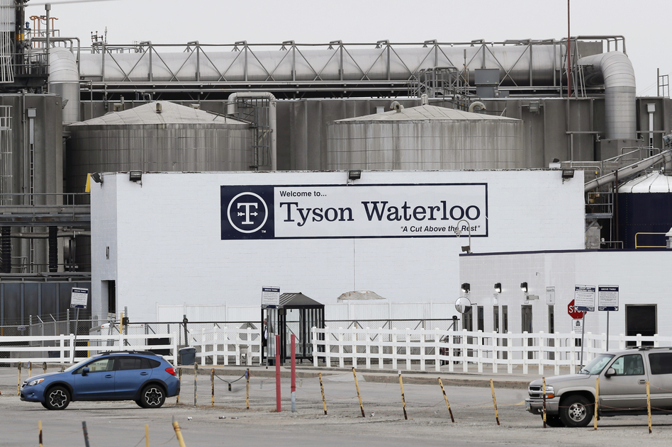 Vehicles sit in a near empty parking lot outside the Tyson Foods plant in Waterloo, Iowa, on May 1. (Charlie Neibergall/AP)