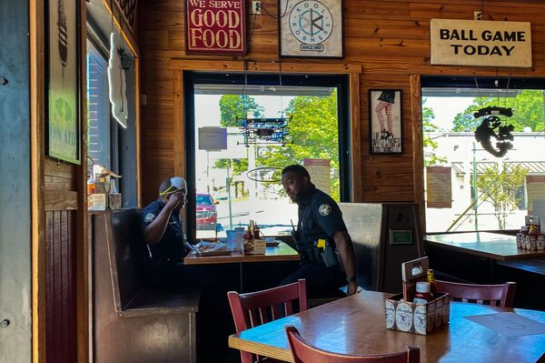 Two police officers get something to eat at Moe's Original BBQ restaurant in late April in Atlanta afte limited dine-in service was allowed under loosened state  coronavirus restrictions.