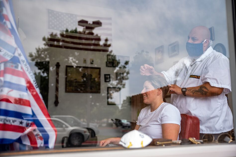 A woman gets a haircut on Friday in Round Rock, Texas, as the state slowly reopens from its pandemic shutdown. (Sergio Flores/AFP via Getty Images)