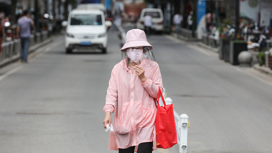 A woman wears a face mask on Monday as she walks along a street in Wuhan, in China's central Hubei province. Wuhan reported new cases of COVID-19 after going more than a month without new infections. (Stringer/AFP via Getty Images)