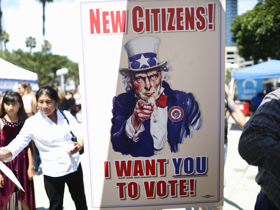 A sign encourages newly sworn-in U.S. citizens to register to vote outside a naturalization ceremony in 2019 in Los Angeles. After failing to get the now-blocked citizenship question on the 2020 census, the Trump administration is continuing to gather government records to produce citizenship data for redistricting. (Mario Tama/Getty Images)