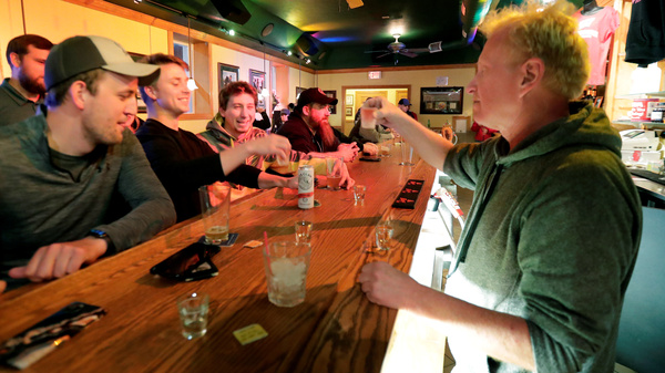 "Bar owner Michael Mattson toasts with patrons as his Friends and Neighbors bar reopens Wednesday in Appleton, Wis. Bars were able to open their doors after the Wisconsin Supreme Court struck down the state's ""Safer at Home"" order."