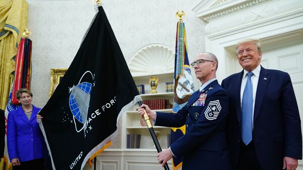U.S. Space Force senior enlisted adviser Chief Master Sgt. Roger Towberman presents the Space Force Flag to President Trump on Friday in the Oval Office.