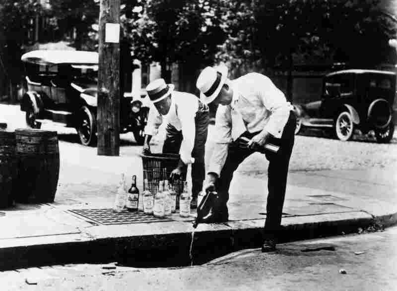 Two men pouring alcohol down a drain during Prohibition. Bootleggers would make their own illegal alcohol with the help of hired chemists. They would remove the toxic contaminants from industrial alcohol, thus making it safe to drink.