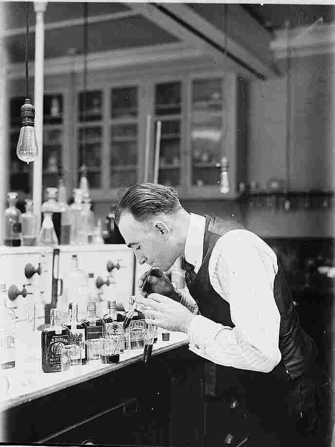 Chemist G.F. Beyer of the Internal Revenue Bureau using a pipette to draw bootleg whiskey for analysis on January 14, 1920. During Prohibition, government chemists added more poisonous contaminants to industrial alcohol, which made it harder for bootleggers to purify. This led to alcohol related deaths of an estimated 10,000 people.