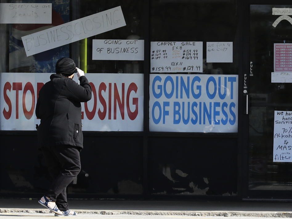 A woman looks at signs at a store in Niles, Ill., on May 13. Shutdowns related to the coronavirus pandemic have left tens of millions out of work. (Nam Y. Huh/AP)