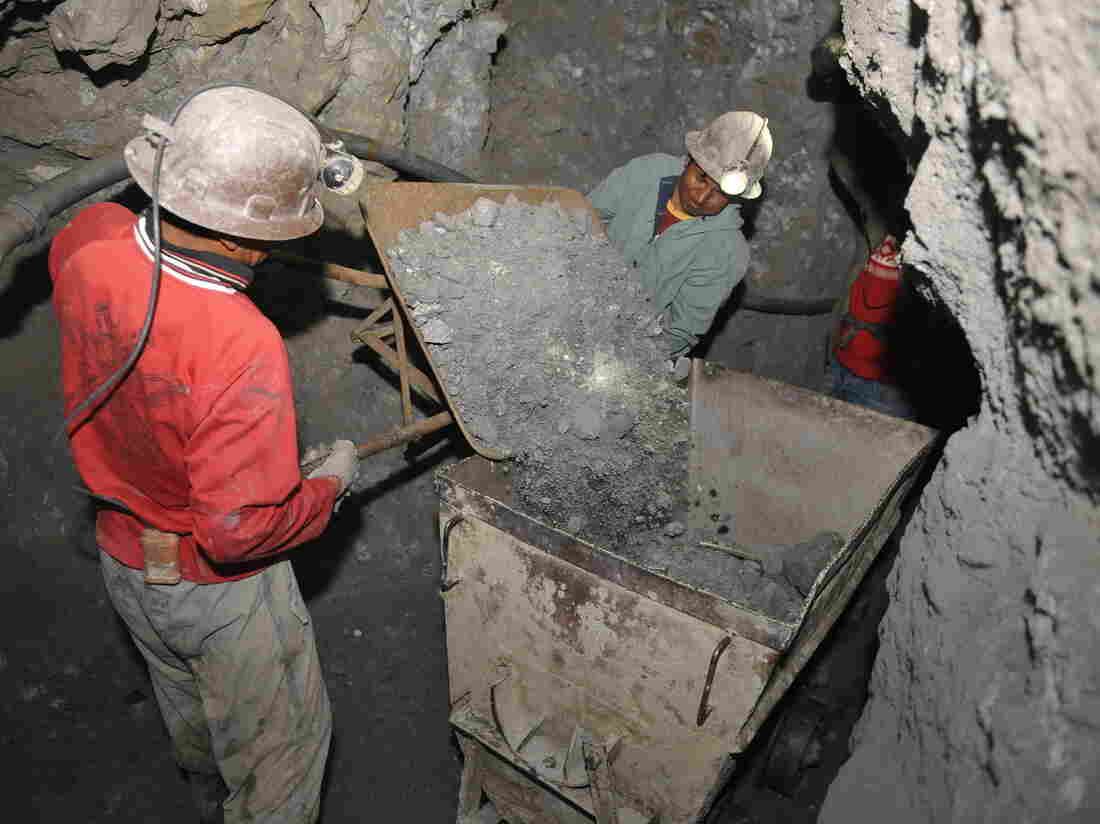 Two miners empty a wheelbarrow with silver ore into a tipping skip in a mine shaft in Cerro Rico hill in Potosi, Bolivia, September 15, 2010. An OIT census in 2001 pointed that in the mines of Cerro Rico hill worked 381 minors of both sexes between 7 and 18 years old. AFP PHOTO/Aizar Raldes (Photo credit should read AIZAR RALDES/AFP via Getty Images)