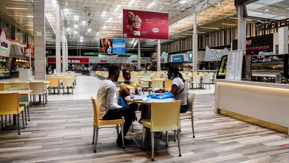 People eat in a deserted food court inside a mall west of Fort Lauderdale, Fla., Monday. U.S. states have been easing restrictions on businesses ahead of Memorial Day, the traditional start of the summer vacation and outdoor season. (Chandan Khanna/AFP via Getty Images)