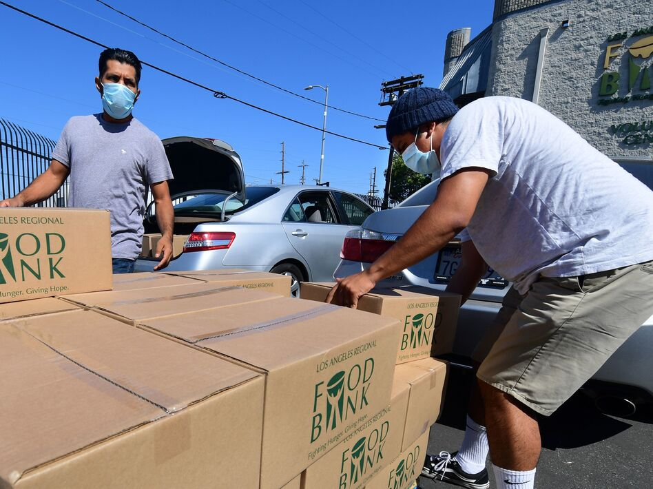 People load their vehicles with boxes of food at a Los Angeles Regional Food Bank earlier this month in Los Angeles. Food banks across the United States are seeing numbers and people they have never seen before amid unprecedented unemployment from the COVID-19 outbreak. (Frederic J. Brown/AFP via Getty Images)