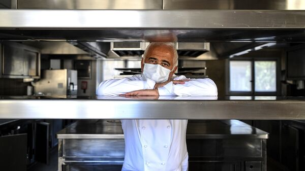 French chef Guy Savoy poses with a face mask in the kitchen of one of his restaurants, in the Monnaie de Paris building, on Tuesday.