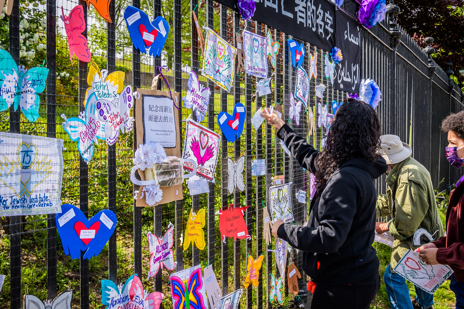 A volunteer artist sets up a memorial May 20 in Brooklyn. Artists and volunteer organizers across New York City put up memorials throughout the five boroughs to honor those who died of COVID-19. (Erik McGregor/LightRocket via Getty Images)