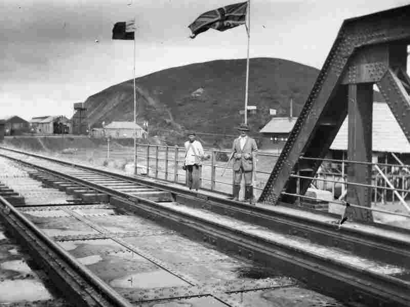 Flags mark the border between Chinese and British territory on the railway bridge in Kowloon, 1910.
