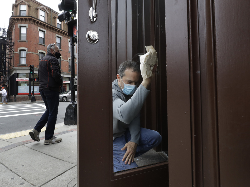 Manager Mike Bonavita wears a protective mask as he cleans windows at the Quattro Italian restaurant in Boston on May 12 during the coronavirus pandemic. This month, Massachusetts' governor declared wearing masks mandatory. (Steven Senne/AP)