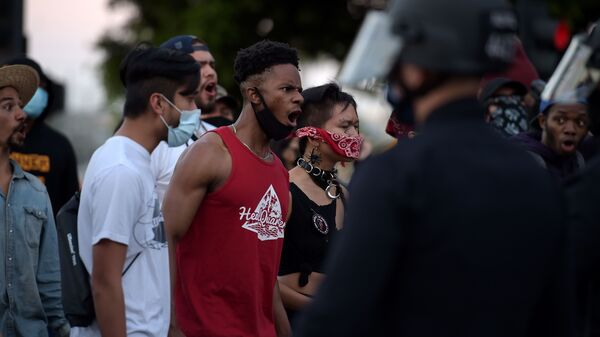 Protesters react in front of police as they gather in downtown Los Angeles on Wednesday to demonstrate after George Floyd, an unarmed black man, died while being arrested by a police officer in Minneapolis who pinned him to the ground with his knee.