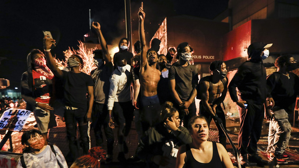 Protesters demonstrate outside the burning 3rd Precinct police building in Minneapolis on Thursday. Protests over the death of George Floyd, a black man who died in police custody Monday, broke out in Minneapolis for a third straight night.