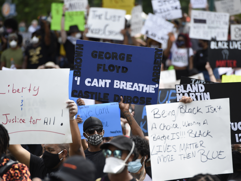 Demonstrators gather Friday in Atlanta's Centennial Olympic Park, one of several protests organized in cities across the United States. (Mike Stewart/AP)