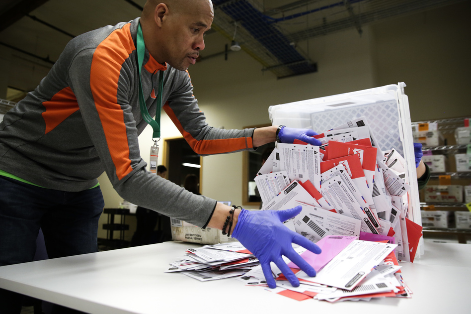 An election worker in Renton, Wash., begins processing mail-in ballots during that state's presidential primary in March. Varying state-by-state requirements around signatures and other rules have become the focus of legal fights as absentee voting expands due to the pandemic. (Jason Redmond/AFP via Getty Images)