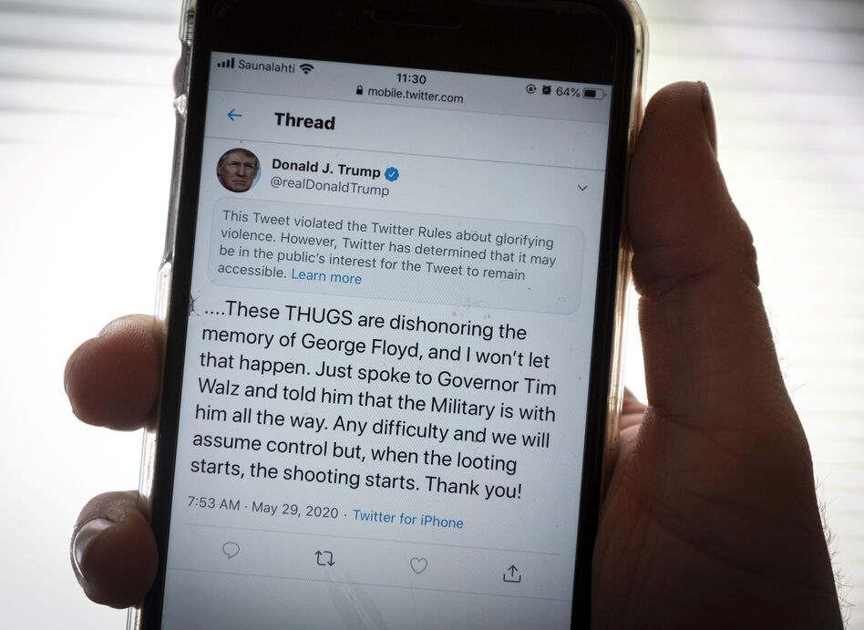 "President Trump's Twitter page is displayed on a mobile phone. The social media company flagged one of his tweets about Minneapolis as ""glorifying violence"" and hid it from public view unless a user clicks on it. (Olivier Morin/AFP via Getty Images)"
