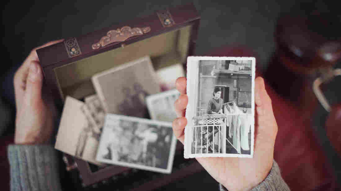 Hands of woman discovering a treasure chest full of photographs and holding an old black and white photograph of a smiling woman standing on a balcony in Milan in 1960s.
