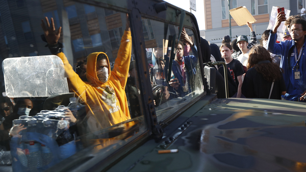 A National Guard vehicle reflects a crowd of protesters Friday in Minneapolis, where Maj. Gen. Jon Jensen said that night