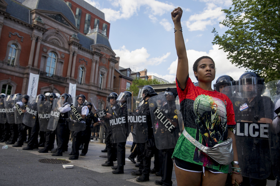 A woman stands in front of a line of police officers near the White House during a protest in Washington, D.C. (Tyrone Turner/WAMU)