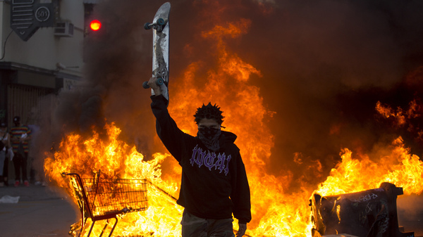 A protester holds a skateboard in front of a fire in Los Angeles, Saturday, May 30, 2020, during a protest over the death of George Floyd.