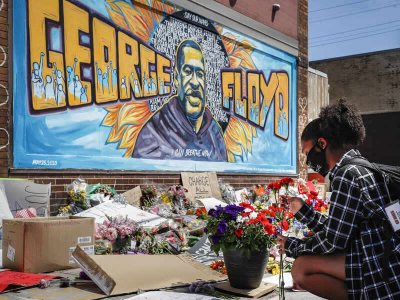 Malaysia Hammond places flowers at a memorial mural for George Floyd in Minneapolis on Sunday. Police brutality has sparked days of civil unrest. But the sparks have landed in a tinderbox built over decades of economic inequality, now exacerbated by the coronavirus pandemic. John Minchillo/AP