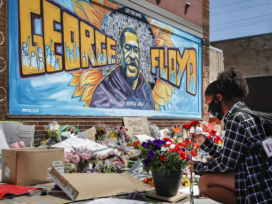 Malaysia Hammond places flowers at a memorial mural for George Floyd in Minneapolis on Sunday. Police brutality has sparked days of civil unrest. But the sparks have landed in a tinderbox built over decades of economic inequality, now exacerbated by the coronavirus pandemic. (John Minchillo/AP)