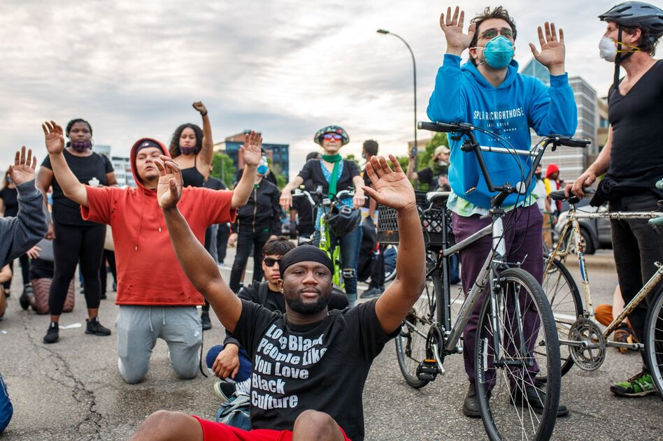Demonstrators kneel and raise their hands during a protest in Minneapolis on Sunday. (Kerem Yucel/AFP via Getty Images)