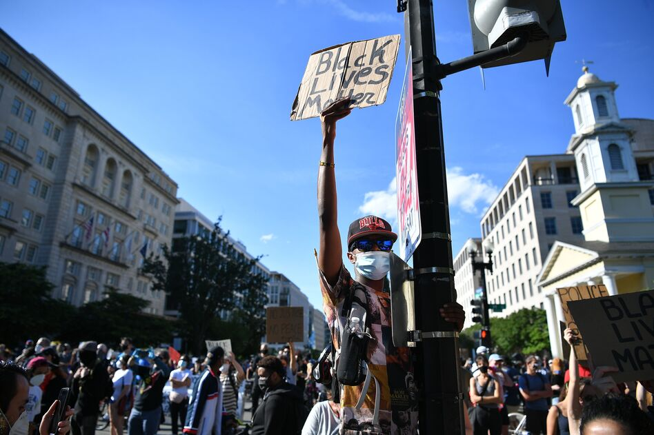 Demonstrators protesting the death of George Floyd hold up placards near the White House on June 1 in Washington, D.C. (Mandel Ngan/AFP via Getty Images)