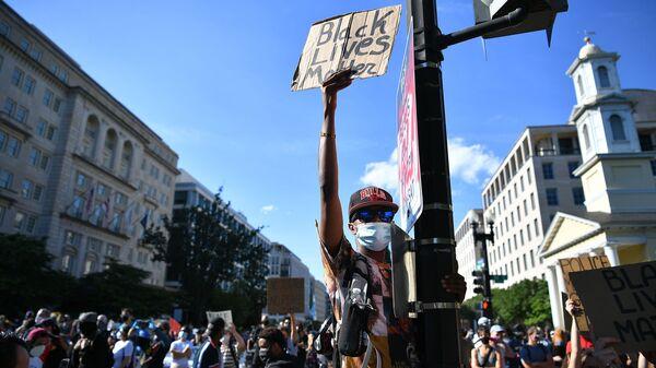 Des manifestants protestant contre la mort de George Floyd brandissent des pancartes près de la Maison Blanche le 1er juin à Washington, D.C.