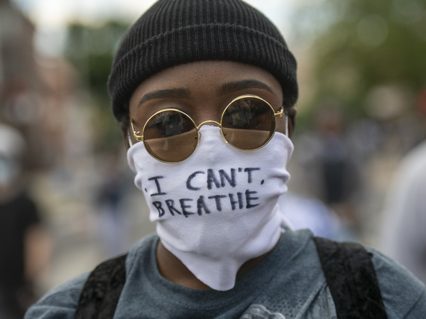 """Protests over police treatment of black people have sparked concerns about the spread of COVID-19. Here, a protester marches Monday in Philadelphia with a cloth mask saying, """"I can't breathe."""""""