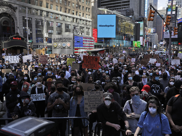 Protesters gather in Times Square before marching through the streets of Manhattan on Monday. New York City imposed an 11 p.m. curfew.