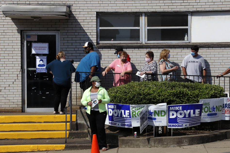 Voters stand in line as they wait to cast their ballots during primary voting in Braddock, Pa., on Tuesday. Problems with absentee ballots and a smaller number of polling places led to long lines in several states as primary elections that were delayed by the coronavirus resumed. (Gene J. Puskar/AP)