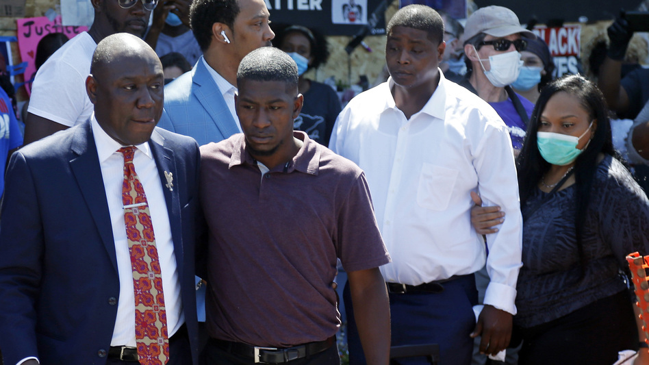 All four former Minneapolis police officers connected with George Floyd's death now face criminal charges. Attorney Ben Crump (left) escorts Floyd's son, Quincy Mason Floyd (second from left), on Wednesday during a visit to the memorial at the site where George Floyd was arrested in Minneapolis. (Jim Mone/AP)