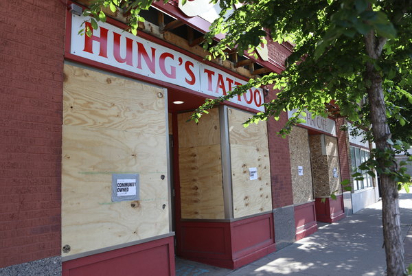 """Boarded-up businesses bear signs that read """"Community Owned"""" in the Frogtown neighborhood of St. Paul, Minn."""
