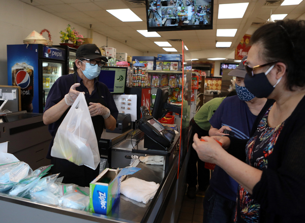Shop owner Si Nguyen rings up customers in his Frogtown market in St. Paul, Minn.