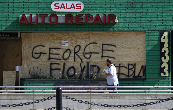 A mail carrier walks by a boarded-up business in the ethnically diverse Frogtown neighborhood of St. Paul, Minn., during continued demonstrations against the killing of George Floyd.