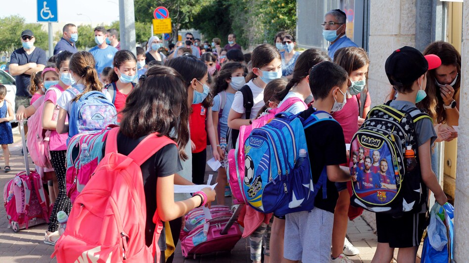 Students wear masks May 17 outside a school in the Israeli city of Modiin. Israeli students in all grades went back to school last month. (Xinhua News Agency/Getty Images)