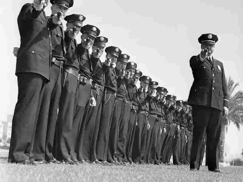 A line of policemen take aim.