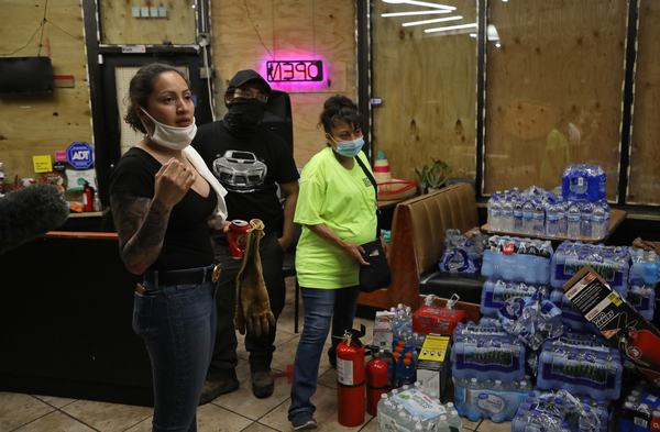 Volunteers with Security Latinos De La Lake secure a business as they work to protect homes and businesses during continued demonstrations over the death of George Floyd, an African American man, by a Minneapolis police officer.