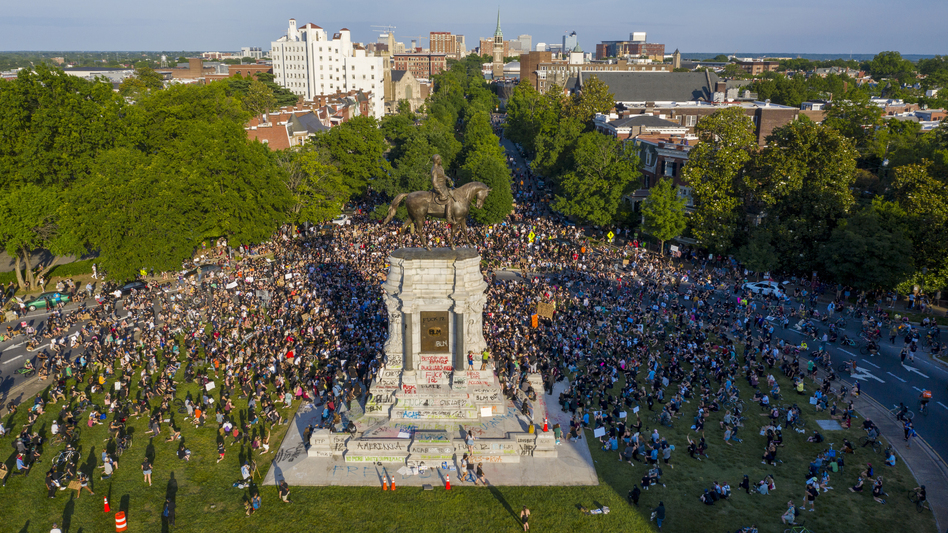 """A large group of protesters gathered around the statue of Confederate Gen. Robert E. Lee, on Tuesday in Richmond, Va. The crowd protesting police brutality chanted, """"Tear it down."""" (Steve Helber/AP)"""