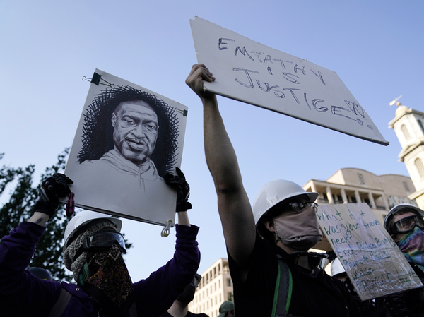 A demonstrator holds a sign with George Floyd's likeness on it as people gather to protest his death and police brutality this week near the White House in Washington.
