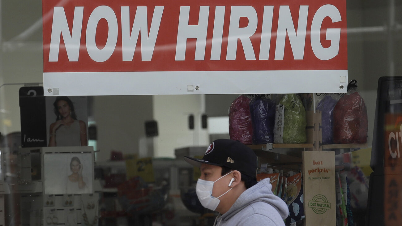 A man walks by a CVS Pharmacy in San Francisco on May 7. U.S. employers unexpectedly added jobs last month as the unemployment rate fell. Jeff Chiu/AP