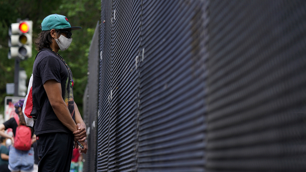 A person stands next to a fence as demonstrators protest Thursday near the White House over the death of George Floyd. The security perimeter is being extended several blocks.