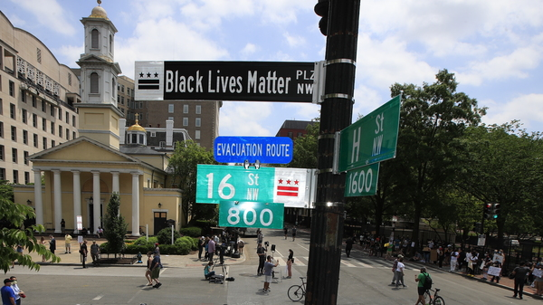 A new street sign sits above an intersection outside St. John