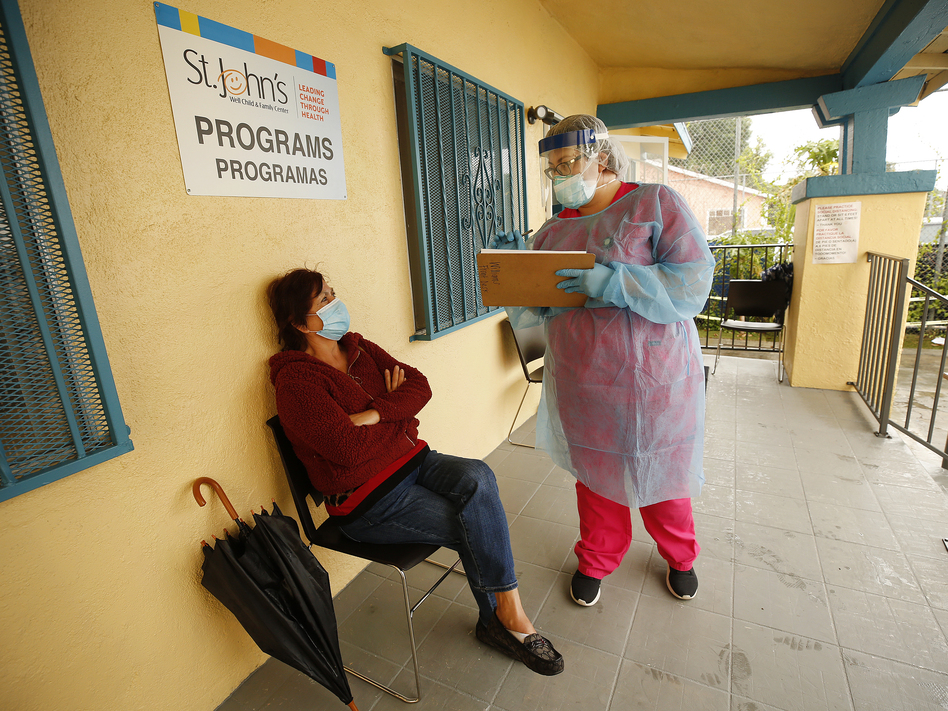 Maria Banderas (left) answers questions from medical assistant Dolores Becerra on May 18 before getting a coronavirus test at St. John's Well Child and Family Center in South Los Angeles, one of the LA neighborhoods hit hard by COVID-19. (Al Seib/LA Times via Getty Images)
