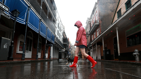 A woman walks her dog through the French Quarter in New Orleans as Tropical Storm Cristobal reaches the U.S., on Sunday.