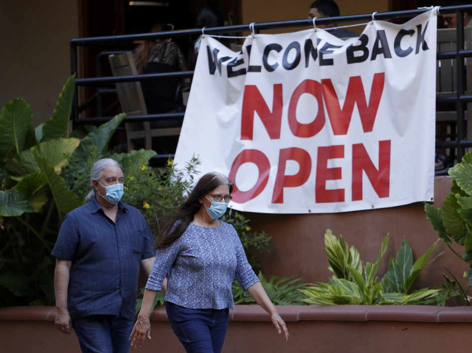 Visitors to the River Walk in San Antonio pass a reopened restaurant on May 18. Texas Gov. Greg Abbott says bars and bowling alleys are on the list of businesses that can reopen at 25% beginning Friday, and restaurants can increase to 50% capacity as the state continues to go through phases to reopen. (Eric Gay/AP)