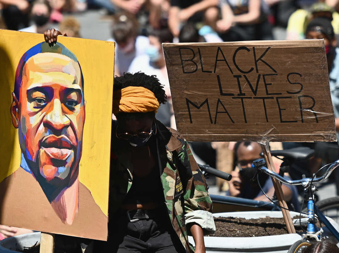 """Protesters hold up signs during a """"Black Lives Matter"""" protest in front of Borough Hall on June 8, 2020 in New York City.  (Photo by ANGELA WEISS/AFP via Getty Images)"""